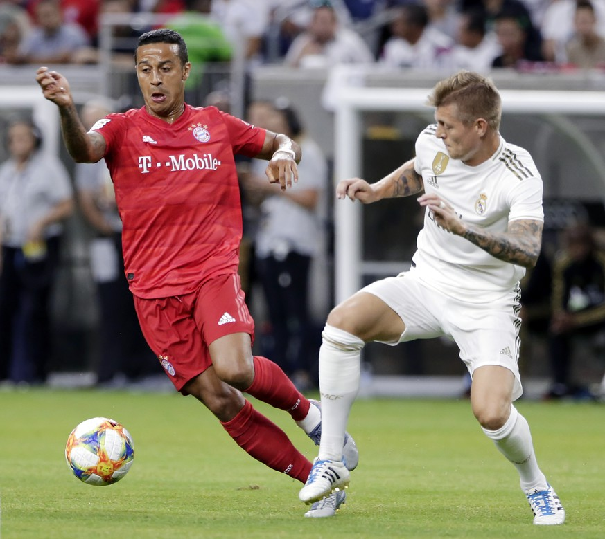 FC Bayern midfielder Thiago, left, moves the ball past Real Madrid midfielder Toni Kroos during the first half of an International Champions Cup soccer match Saturday, July 20, 2019, in Houston. (AP Photo/Michael Wyke)