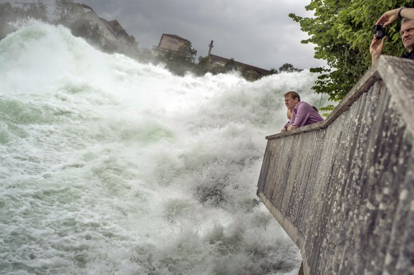 Ein Paar staunt ueber die gewaltigen Wassermassen des Rheinfalls bei Neuhausen (SH) am Dienstag, 16. Juni 2015. (KEYSTONE/Walter Bieri)  People marvel at the mighty waters of the Rhine Falls in Neuhausen, Schaffhause, Switzerland, on Tuesday June 16 2015. (KEYSTONE/Walter Bieri)