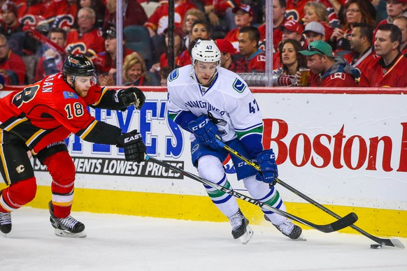 Apr 25, 2015; Calgary, Alberta, CAN; Vancouver Canucks left wing Sven Baertschi (47) and Calgary Flames center Matt Stajan (18) battle for the puck during the second period in game six of the first round of the 2015 Stanley Cup Playoffs at Scotiabank Saddledome. Mandatory Credit: Sergei Belski-USA TODAY Sports