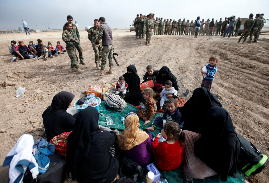 Displaced Iraqi women and children sit near Kurdish Peshmerga fighters after escaping from the Islamic State-controlled village of Abu Jarboa, Iraq October 31, 2016. REUTERS/Azad Lashkari