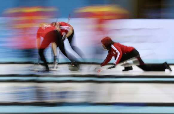Switerland's skip Mirjam Ott, right, delivers the rock to her teammates during the women's curling competition against Sweden at the 2014 Winter Olympics, Thursday, Feb. 13, 2014, in Sochi, Russia. (AP Photo/Wong Maye-E)