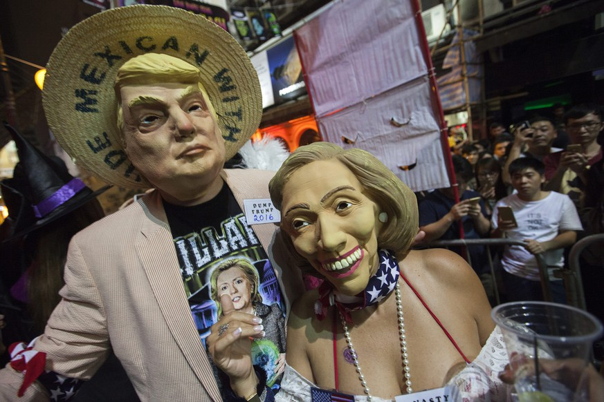 epa05611585 People dressed up as US Republican presidential candidate Donald Trump (L) and US Democratic presidential candidate Hillary Clinton for Halloween celebrate in Hong Kong's popular bar disrict of Lan Kwai Fong, Hong Kong, China, 31 October 2016.  EPA/ALEX HOFFORD