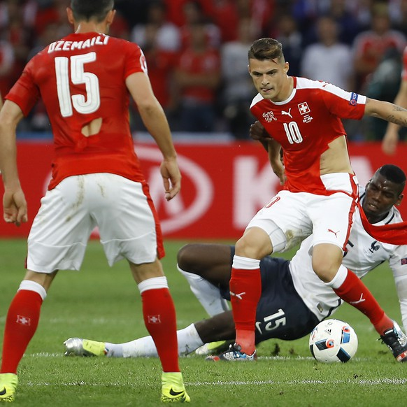 Switzerland's Blerim Dzemaili, left, and Granit Xhaka play with ripped jerseys during the Euro 2016 Group A soccer match between Switzerland and France at the Pierre Mauroy stadium in Villeneuve d'Ascq, near Lille, France, Sunday, June 19, 2016. (AP Photo/Darko Vojinovic)