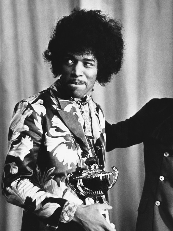 1st October 1967:  Influential rock guitarist, singer and songwriter Jimi Hendrix  (1942 - 1970) holds an award which he has just received from Radio One DJ Jimmy Savile.  (Photo by Express/Express/Getty Images)