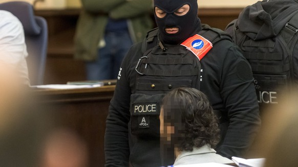 epa06497778 Prime suspect in the November 2015 Paris attacks Salah Abdeslam (R) sits as he is surrounded by Belgian special police officers  in the courtroom prior to the opening of the trial of terror suspects Salah Abdeslam and Sofiane Ayari, also known as Amine Choukri, in Brussels, Belgium, 05 February 2018. Terrorist suspects Salah Abdeslam and Sofiane Ayari are on trial for attempted murder of police searching for suspects of the November 2015 Paris terror attacks that left 130 people dead, when Abdeslam was on the run and hiding in the Belgian capital. Abdeslam allegedly escaped a shootout with Belgian police in March 2016 during which he wounded four officers but was captured and arrested some days later in downtown Brussels. The trial in Belgium only deals with the shootout prior to the arrest. His role in the Paris terrorist attacks will be tried in a court in France at a later stage.  EPA/DANNY GYS / POOL