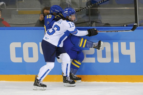 Finland's Hanna-Riikka Valila (front) checks Sweden's Emilia Andersson (10) into the boards during the first period of their women's ice hockey playoffs quarter-final game at the Sochi 2014 Winter Olympic Games February 15, 2014. REUTERS/Laszlo Balogh (RUSSIA  - Tags: SPORT ICE HOCKEY OLYMPICS)