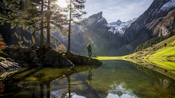 epa06289138 A hiker enjoys the view of the mountain Saentis at the Seealpsee lake, in the canton of Appenzell Innerrhoden, Switzerland, on 25 October  2017.  EPA/CHRISTIAN MERZ