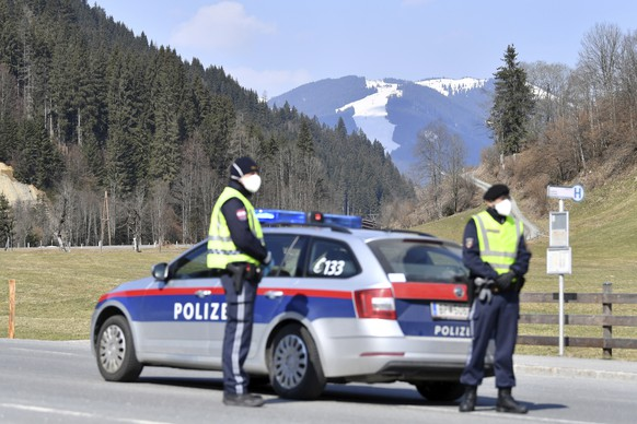 Police blogs the road to the skying resort Saalbach Hinterglemm, Austrian province of Salzburg, Friday, April 3, 2020 after the city was quarantined.The Austrian government has moved to restrict freedom of movement for people, in an effort to slow the onset of the COVID-19 coronavirus. (AP Photo/Kerstin Joensson)