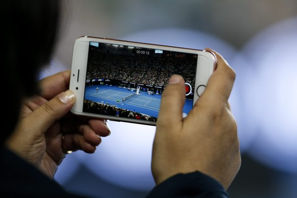 epa05754105 A spectator uses her phone during the Men's Singles semi-final match between Rafael Nadal of Spain and Grigor Dimitrov of Bulgaria at the Australian Open Grand Slam tennis tournament in Melbourne, Victoria, Australia, 27 January 2017.  EPA/LYNN BO BO