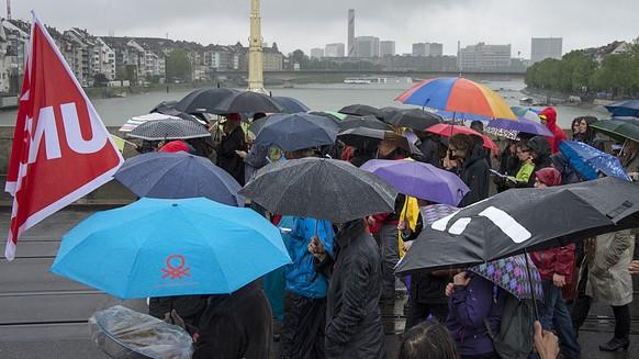 Demonstranten mit Regenschirmen marschieren bei stroemendem Regen ueber die Mittlere Bruecke beim traditionellen 1. Mai-Umzug am Freitag, 1. Mai 2015, dem Tag der Arbeit, in Basel. (KEYSTONE/Georgios Kefalas)