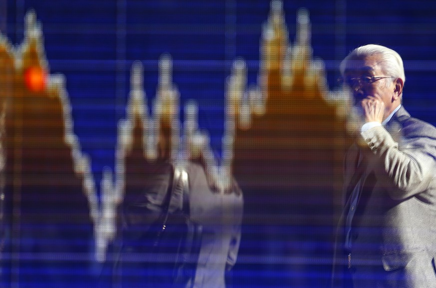 A man is reflected on an electronic stock indicator of a securities firm in Tokyo Wednesday, Nov. 4, 2015. Hong Kong led gains in Asian stock markets Wednesday after an official said China will set up a second stock trading link with the city this year while Japan surged on a blockbuster share sale. (AP Photo/Shizuo Kambayashi)