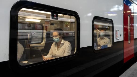 Reisende mit Schutzmasken in einem Zug am Bahnhof SBB in Basel, am Montag, 6. Juli 2020. Das Schutzkonzept gegen das Coronavirus wurde angepasst: Alle Reisenden muessen in oeffentlichen Verkehrsmitteln eine Maske tragen. (KEYSTONE/Georgios Kefalas)