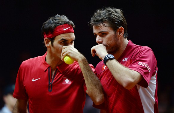 Switzerland's Stanislas Wawrinka (R) whispers to teammate Roger Federer during the doubles tennis match on the second day of the Davis Cup final between France and Switzerland at the Stade Pierre Mauroy in Villeneuve-d'Ascq, northern France, on November 22, 2014.   AFP PHOTO / DENIS CHARLET