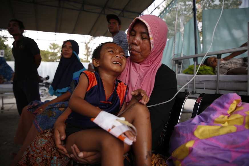 epa06940275 A mother holds her six-years old son, Lalu Azham at an emergency hospital in Tanjung northern Lombok, West Nusa Tenggara, Indonesia, 10 August 2018. According to media reports, a 7.0 magnitude quake hit Indonesia's island of Lombok on 05 August, killing at least 159 people. Additional media reports state that on 09 August 2018, Lombok was hit by a strong tremor which the United States Geological Survey (USGS) said had a magnitude of 5.9, and caused structural damage.  EPA/ADI WEDA