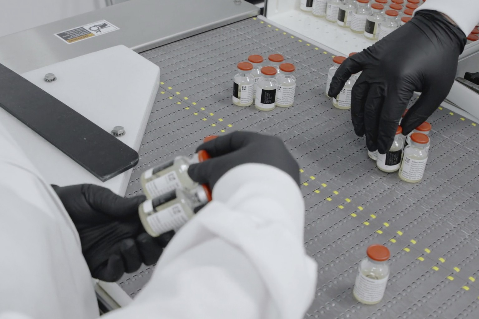 In this undated image from video provided by Regeneron Pharmaceuticals on Friday, Oct. 2, 2020, vials are inspected at the company's facilities in New York state, for efforts on an experimental coronavirus antibody drug. Antibodies are proteins the body makes when an infection occurs; they attach to a virus and help the immune system eliminate it. (Regeneron via AP)