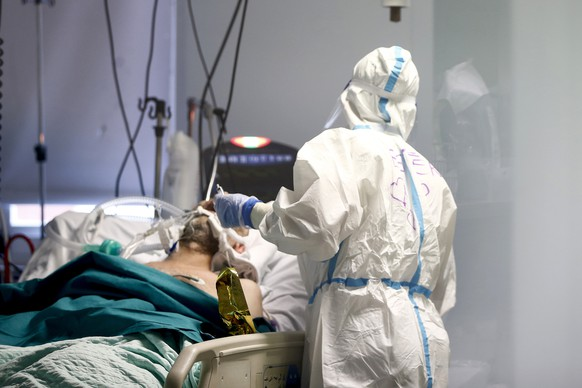 A medical staff tends to a patient inside the COVID-19 intensive care unit at the San Filippo Neri hospital in Rome, Tuesday, Nov. 3, 2020. Italy has registered its highest one-day increase in COVID-19 deaths in six months, with 353 more deaths in the last 24 hours, according to Health Ministry figures on Tuesday. (Cecilia Fabiano/LaPresse via AP)