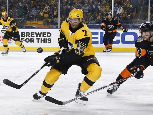 Pittsburgh Penguins' Matt Cullen (7) and Philadelphia Flyers' Shayne Gostisbehere (53) vie for the puck during the first period of an NHL Stadium Series hockey game at Heinz Field in Pittsburgh, Saturday, Feb. 25, 2017. (AP Photo/Gene J. Puskar)