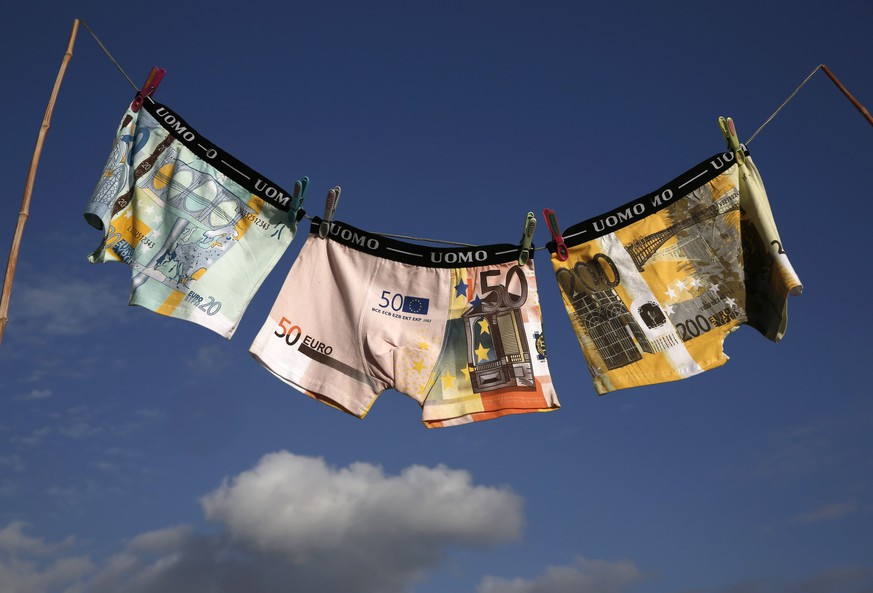 Underwear printed with images of euro banknotes are seen on a washing line, in this picture illustration taken in Athens November 9, 2014. A year-long investigation into allegations of collusion and manipulation by global currency traders is set to come to a head on Wednesday, with Britain's financial regulator and six big banks expected to agree a settlement involving around £1.5 billion ($2.38 billion) in fines. The settlement comes amid a revival of long-dormant volatility on the foreign exchanges, where a steady rise of U.S. dollar this year has depressed oil prices and the currencies of many commodity exporters such as Russia's rouble, Brazil's real and Nigeria's naira - setting the scene for more turbulence on world financial markets in 2015. Picture taken November 9, 2014. REUTERS/Yorgos Karahalis  (GREECE - Tags: BUSINESS CRIME LAW POLITICS)