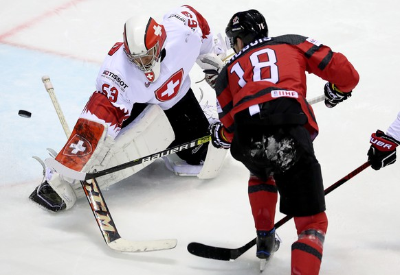 epa07594513 Pierre-Luc Dubois of Canada (R) in action with goalkeeper Leonardo Genoni of Switzerland during the IIHF World Championship quarter final ice hockey match between Canada and Switzerland at the Steel Arena in Kosice, Slovakia, 23 May 2019.  EPA/MARTIN DIVISEK