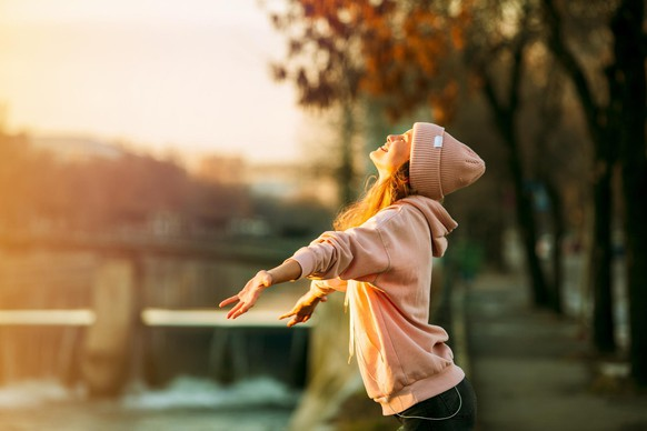 cool hipster young girl in pink hoodie standing by a river in the city very happy smiling to the sun and enjoying it, on autum or springtime