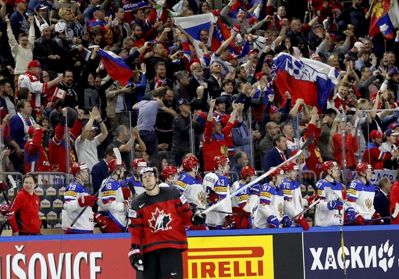 Russia's players celebrate a goal by Yevgeni Kuznetsov as Canada's Travis Konecny skates by at the Ice Hockey World Championships semifinal match between Canada and Russia in the LANXESS arena in Cologne, Germany, Saturday, May 20, 2017. (AP Photo/Petr David Josek)