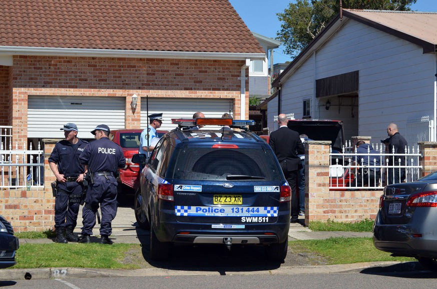 Forensic experts collect evidence from a car outside a house in the Guildford area of Sydney on September 18, 2014. Australia's largest ever counter-terrorism raids detained 15 people and disrupted plans to