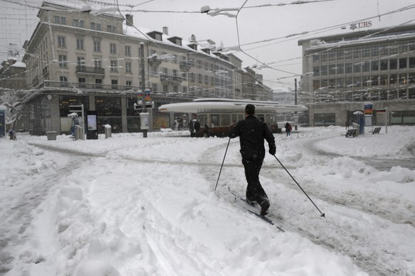 A man on cross-country skis crosses the Paradeplatz in the financial center of Zurich after heavy snowfalls in Zurich, Switzerland, Friday, January 15 2020. The traffic situation is difficult after persistend snowfalls in eastern and central Switzerland.  (KEYSTONE/Alexandra Wey)