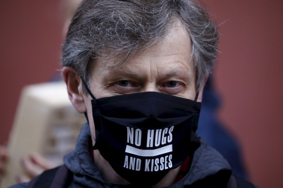epa08743190 A man with face mask reading 'No Hugs and Kisses' attends the flash mob 'Wall of Misunderstanding' protest action next to the parliament building in Riga, Latvia, 14 October 2020. During the flash mob musicians, artists, authors and other creative professionals built a symbolic wall to protest against planned royalty tax rising.  EPA/TOMS KALNINS