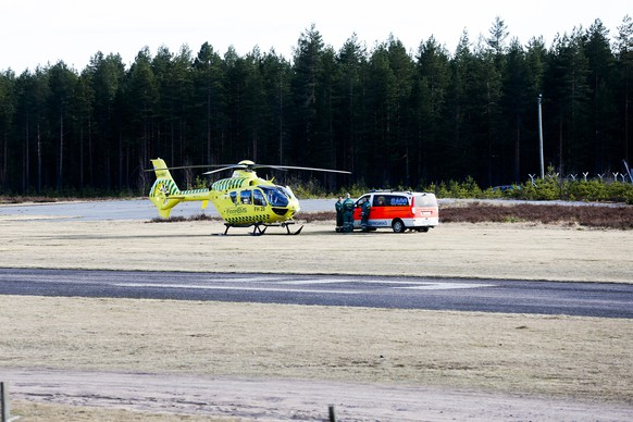 A helicopter and an ambulance are seen at the Jamijarvi Airfield, southwest Finland, on Sunday April 20, 2014. A small passenger plane carrying parachuters fell to the ground near the airfield on Sunday afternoon. The police say that there are more than three victims. Three people out of 11 on the plane were rescued. (AP Photo/Mika Kanerva, Lehtikuva)     FINLAND OUT
