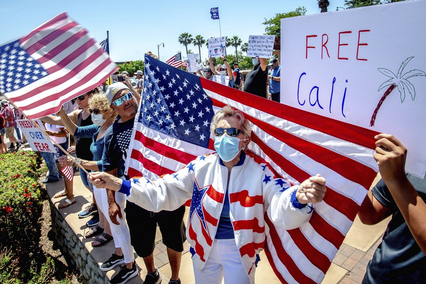 Jan Clever, 81, center, of Rancho Cucamonga, center, waves a U.S. flag while wearing a protective mask during a demonstration against California's stay-at-home orders that were put in place due to the coronavirus outbreak, in Rancho Cucamonga, Calif., Sunday, May 3, 2020. (Watchara Phomicinda/The Orange County Register via AP)