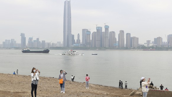 Residents visit the Yangtze River in Wuhan in central China's Hubei province Monday, March 29, 2021. A joint WHO-China study on the origins of COVID-19 says that transmission of the virus from bats to humans through another animal is the most likely scenario and that a lab leak is