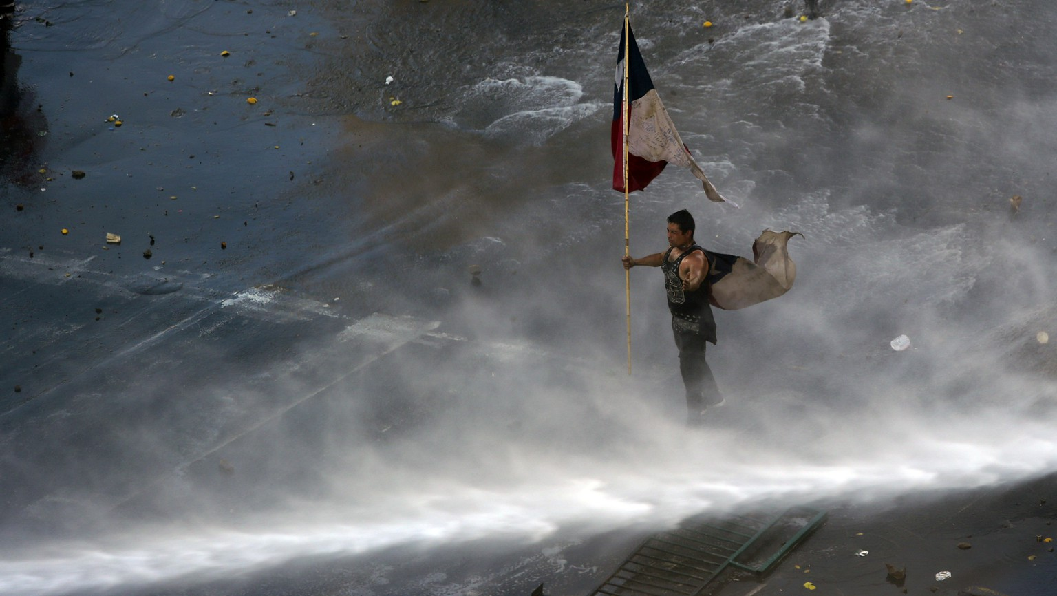"Holding a Chilean flag, a protester braces against a water canon sprayed from a police truck amid a march by students and union members in Santiago, Chile, Monday, Oct. 21, 2019. Protesters defied an emergency decree and confronted police in Chile's capital on Monday, continuing disturbances that have left at least 11 dead and led the president to say the country is ""at war."" (AP Photo/Miguel Arenas)"