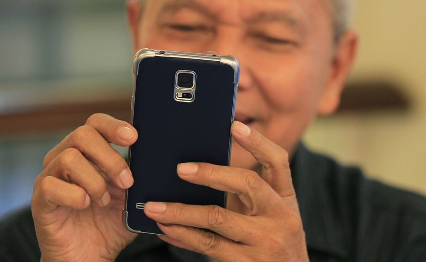 A man reacts while trying out his new Samsung Galaxy S5 in Jakarta, April 11, 2014. Samsung Electronics Co Ltd estimated that its January-March operating profit fell by 4.3 percent to 8.4 trillion won ($7.96 billion) as easing smartphone sales growth continued to weigh earnings down. REUTERS/Beawiharta (INDONESIA - Tags: BUSINESS SOCIETY)