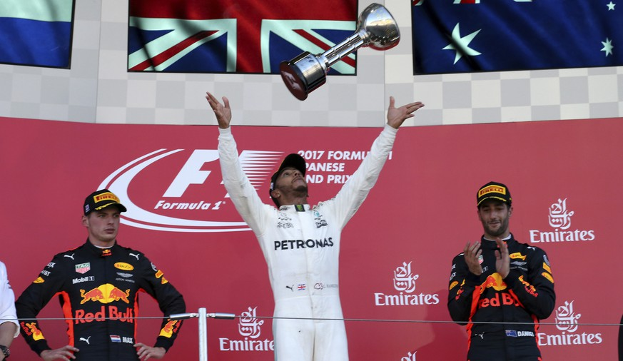 Mercedes driver Lewis Hamilton of Britain throws his trophy as he celebrates on the podium after winning the Japanese Formula One Grand Prix at Suzuka, Japan, Sunday, Oct. 8, 2017. Second placed Red Bull driver Max Verstappen of the Netherlands, left, and teammate Daniel Ricciardo of Australia right was third. (AP Photo/Toru Takahashi)
