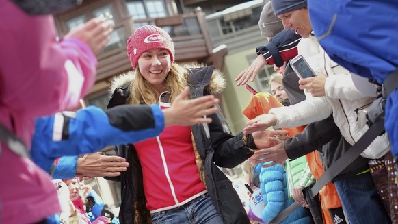In this March 28, 2014 photo, Olympic gold medalist Mikaela Shiffrin walks through the crowd of fans giving high fives as she approaches the stage in Vail, Colo. Mikaela Shiffrin is adding a new twist to the usual relationship between star athlete and worshipping fans. She's putting the spotlight on the fans. The overall World Cup skiing leader and two-time Olympic champion has quietly started a social media campaign labeled (hashstag) IAmYourBiggestFan to draw attention to some of the supporters who inspire her. (AP Photo/The Vail Daily, Anthony Thornton, File )