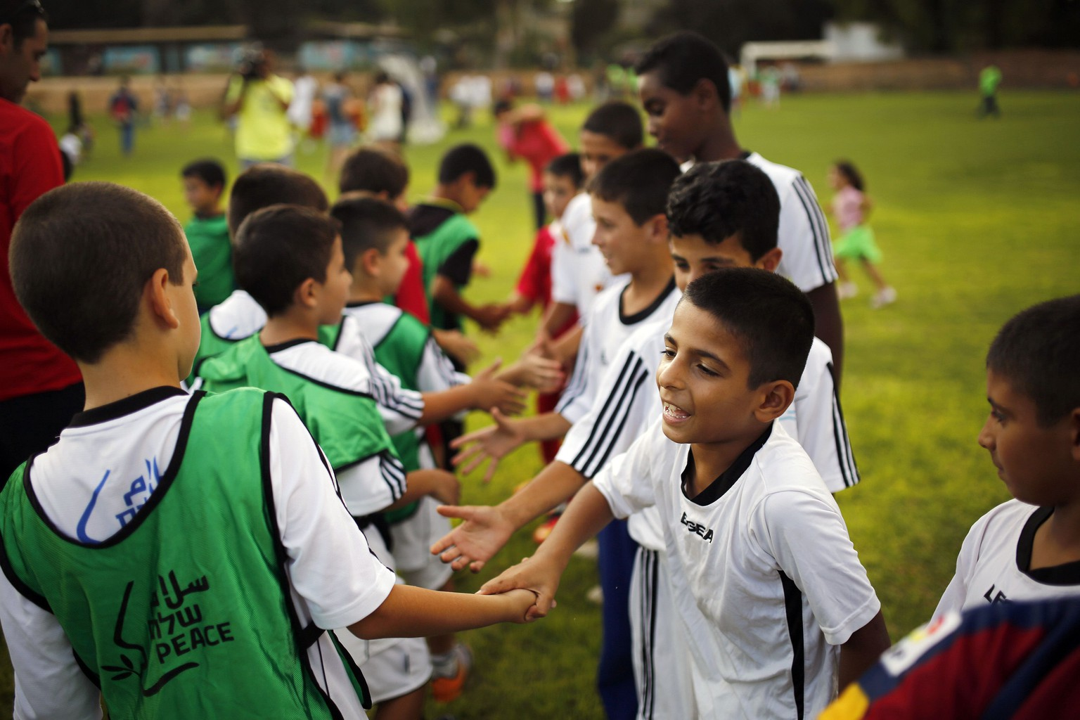 Israeli and Palestinian children shake hands during an event opening a year of training of an Israeli-Palestinian soccer program launched by the Peres Center for Peace, in Kibbutz Dorot, outside the Gaza Strip, September 1, 2014. An open-ended ceasefire in the Gaza war has held since August 27. Some 80 children from communities near the Gaza border and from the West Bank Palestinian village of Yatta took part in the training session, the first since the ceasefire started. REUTERS/Amir Cohen (ISRAEL - Tags: POLITICS EDUCATION SPORT SOCCER TPX IMAGES OF THE DAY)