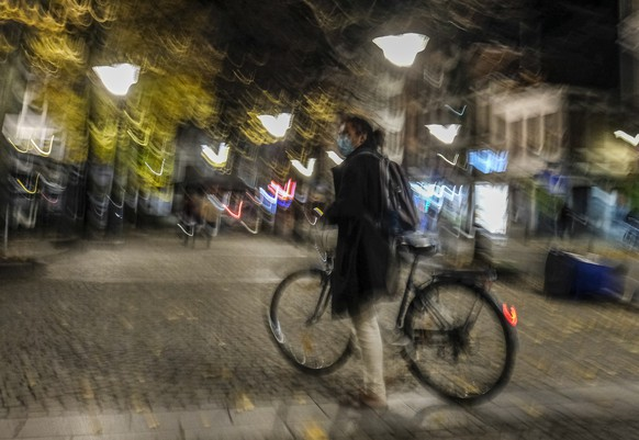 epa08771259 A man with his bike in a almost empty street before a city night time curfew scheduled at 22h in Liege, Belgium, 24 October 2020. Walloon region announced on 23 October a curfew from 22h until 06h as the measure will be in effect from 24 October evening until 19 November 2020. New measures have been taken also in Brussels such as the curfew extended from 22h until 06h, the mask again compulsory everywhere, cultural and sports venues closed.  EPA/JULIEN WARNAND