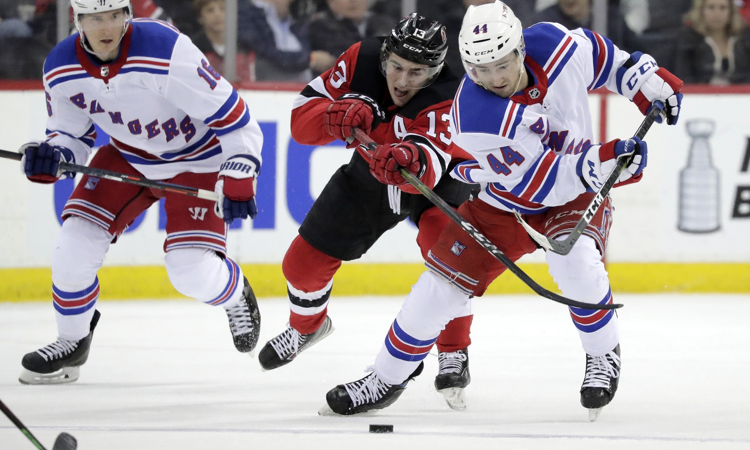 New Jersey Devils center Nico Hischier (13), of Switzerland, competes for the puck with New York Rangers defenseman Neal Pionk (44) during the third period of an NHL hockey game, Monday, April 1, 2019, in Newark, N.J. The Devils won 4-2. (AP Photo/Julio Cortez)