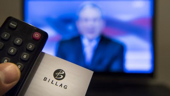 """ARCHIVBILD ZUR NEUVERGABE DES MANDATS ZUER ERHEBUNG DER RADIO- UND TV-ABGABE DURCH DEN BUND AN DIE SERAFE AG, AM FREITAG, 10. MAERZ 2017 ---- Une personne tient dans sa main une telecommande ainsi qu'un document de l'entreprise responsable de la perception de la redevance, Billag, devant un ecran de television montrant l'emission le """"Telegiornale"""" de la RSI ce lundi 6 mars 2017 a Lausanne. Le Conseil des Etats se prononcera mercredi sur l'initiative populaire """"No Billag"""" qui demande la suppression de la redevance. Et la semaine prochaine, le Conseil national se penchera sur la mission et les moyens financiers du service public regroupees au sein de la SRG SSR. (KEYSTONE/Jean-Christophe Bott)"""