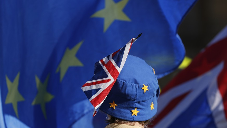 A pro-EU demonstrator wears an EU flag styled as a hat, with a British Union flag pinned to it, outside the Palace of Westminster as the British government holds a cabinet meeting on Brexit inside 10 Downing Street, London, Tuesday, Oct. 16, 2018. The Brexit agreement must be sealed in the coming weeks to leave enough time for relevant parliaments to ratify it, but talks continue, particularly over how to ensure no physical border dividing the UK from Northern Ireland and the EU member state of Ireland. (AP Photo/Alastair Grant)