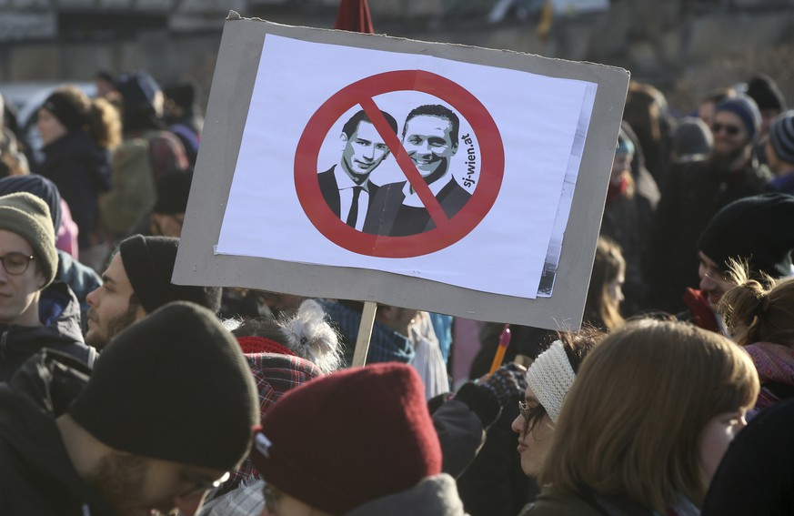 Protestors hold a poster with new Chancellor Sebastian Kern and new Vice Chancellor Heinz-Christian Strache at a demonstration during the swearing-in ceremony of the new Austrian government led by a conservative and a nationalist party in Vienna, Austria, Monday, Dec. 18, 2017. (AP Photo/Ronald Zak)