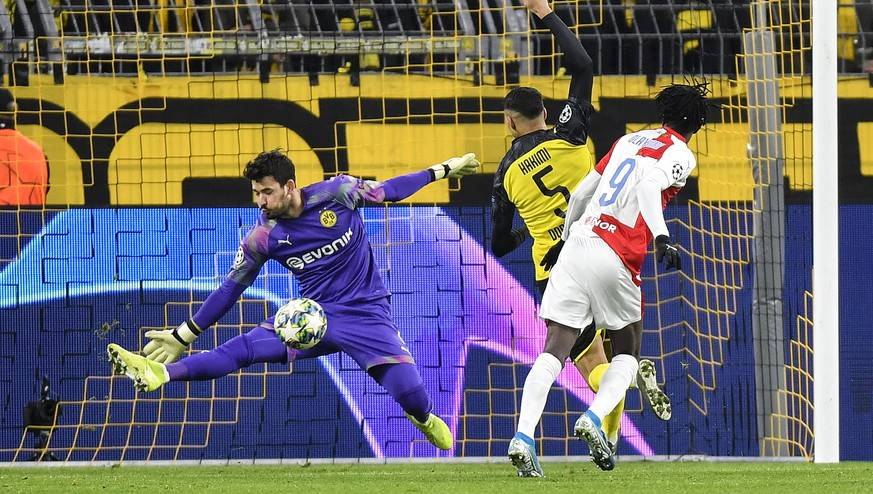 Dortmund's goalkeeper Roman Buerki saves a ball kicked by Slavia's Peter Olayinka, right, during the Champions League Group F soccer match between Borussia Dortmund and Slavia Praha in Dortmund, Germany, Tuesday, Dec. 10, 2019. (AP Photo/Martin Meissner)
