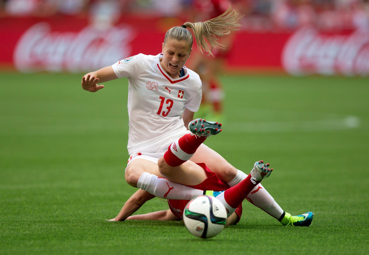 Switzerland's Ana Maria Crnogorcevic (13) and Canada's Allysha Chapman collide during the first half of the FIFA Women's World Cup soccer action in Vancouver, British Columbia, Canada, on Sunday, June 21, 2015 . (Darryl Dyck/The Canadian Press via AP) MANDATORY CREDIT