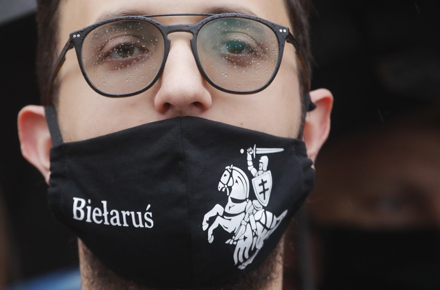 Belarusian opposition supporter wearing a face mask with an old Belarusian national emblem attends a protest rally in front of the government building at Independent Square in Minsk, Belarus, Wednesday, Aug. 19, 2020. The authoritarian leader of Belarus complained that encouragement from abroad has fueled daily protests demanding his resignation as European Union leaders held an emergency summit Wednesday on the country's contested presidential election and fierce crackdown on demonstrators. (AP Photo/Dmitri Lovetsky)
