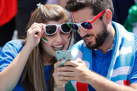 Italy supporters look at a cellphone on the stands before the Euro 2016 Group E soccer match between Italy and Sweden at the Stadium municipal in Toulouse, France, Friday, June 17, 2016. (AP Photo/Andrew Medichini)