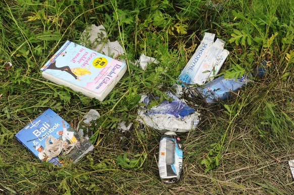 A picture taken on July 18, 2014 shows belongings of passengers on the site of the crash of the Malaysia Airlines jet carrying 298 people from Amsterdam to Kuala Lumpur a day after it crashed, near the town of Shaktarsk, in rebel-held east Ukraine. Pro-Russian rebels fighting central Kiev authorities claimed on July 17 that the Malaysian airline that crashed in Ukraine had been shot down by a Ukrainian jet. All 298 people on board Flight MH17 died when the plane crashed. AFP PHOTO /DOMINIQUE FAGET