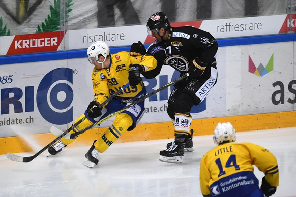 Davos's player Dario Simion, left, fights for the puck with Lugano's player Alessandro Chiesa, right, during the preliminary round game of National League Swiss Championship 2017/18 between HC Lugano and HC Davos, at the ice stadium Resega in Lugano, Switzerland, Saturday, October 14, 2017. (KEYSTONE/Ti-Press/Pablo Gianinazzi)