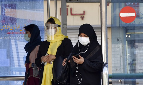 epa08744198 Iranian women wearing face masks wait in a bus station in a street of Tehran, Iran, 14 October 2020. According to the Iranian Health ministry, Iran reported its highest daily COVID-19 death toll by announcing 279 dead and 4830 new infections in the past 24 hours as it appears that Iran is in the grip of a third wave of COVID-19 outbreak.  EPA/ABEDIN TAHERKENAREH