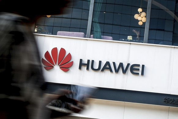 FILE - In this July 30, 2019, file photo a woman walks by a Huawei retail store in Beijing. U.S. regulators are proposing to cut off funding for Chinese equipment in U.S. networks, citing security threats..The proposal would mean that telecom companies receiving government subsidies can't use those to pay for networking equipment from Huawei and ZTE. (AP Photo/Andy Wong, File)