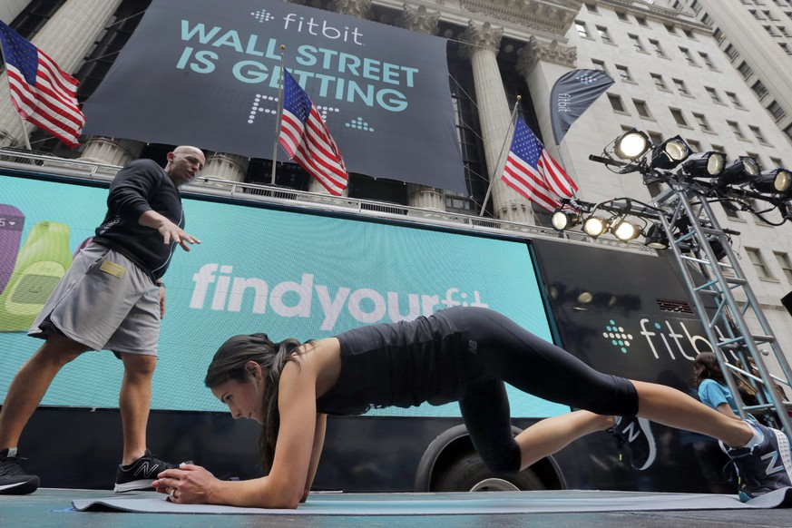 Fitness expert Harley Pasternak, left, and actress Jordana Brewster lead a work out on behalf of Fitbit, in front of the New York Stock Exchange, Thursday, June 18, 2015. Fitbit flexed some muscle Thursday and its shares rocketed 50 percent higher in the first day of trading for the fitness tracking gear maker. (AP Photo/Richard Drew)